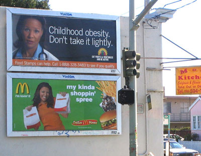 A public service announcement about childhood obesity is posted above a McDonald's billboard.